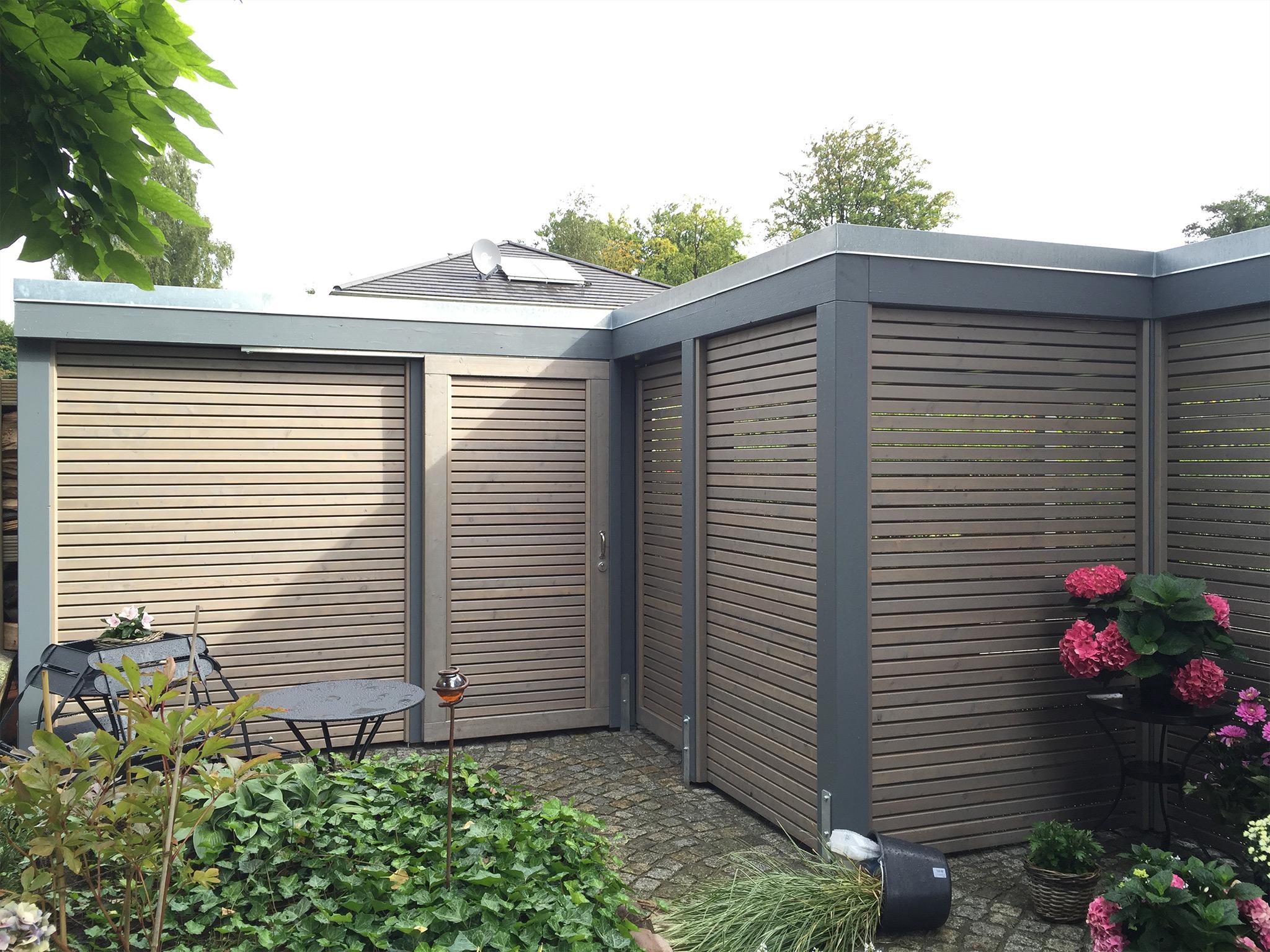 Design-Carport aus Holz mit grauen Pfosten, grauer Blende, Alu-Abdeckprofil und Rhombuswänden offen mit integrierter Schiebetür
